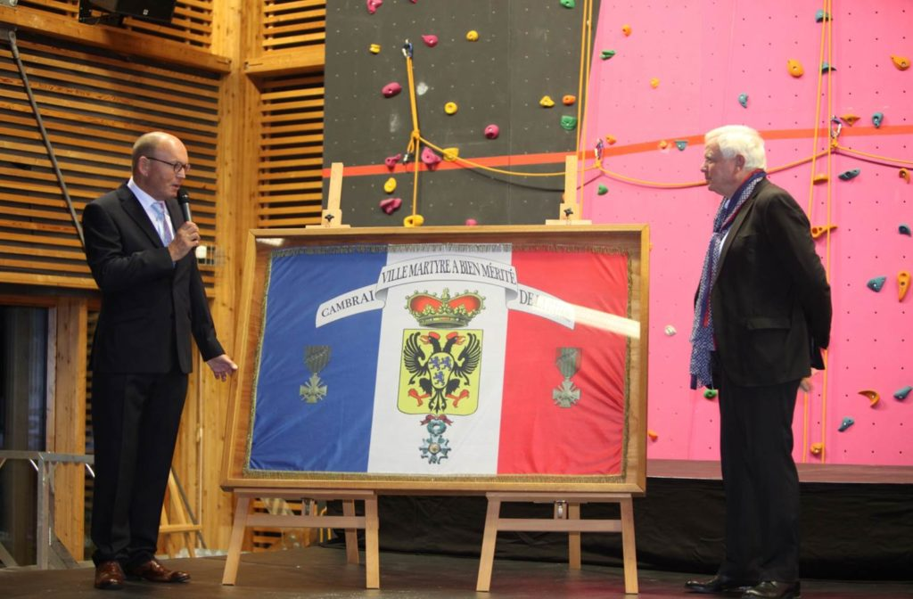 passage du drapeau commémoratif entre Messieurs Bauduin et Van der Henst
